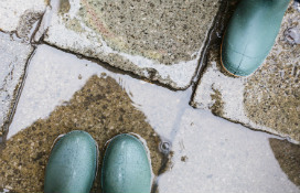 green-rain-boots-in-puddle-on-paving-stones